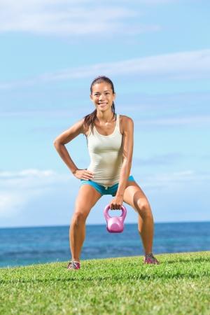 arracher: Femme Crossfit exercice de remise en forme de levage de kettlebell entra�nement de la force au cours de l'exercice en plein air sur l'herbe pr�s de l'oc�an. Belle jeune instructeur fitness faisant un bras oscillant ou kettlebell arrach�.