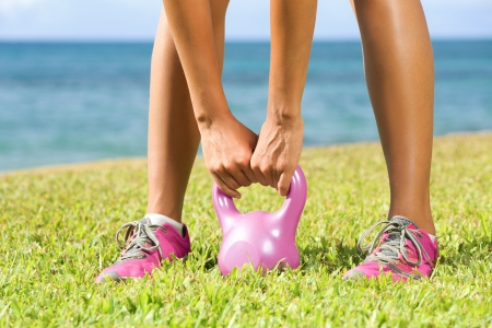 crossfit: Fitness - kettlebell crossfit woman cross training outside on crass lifting kettlebells. Closeup of hands lifting pink kettlebell.