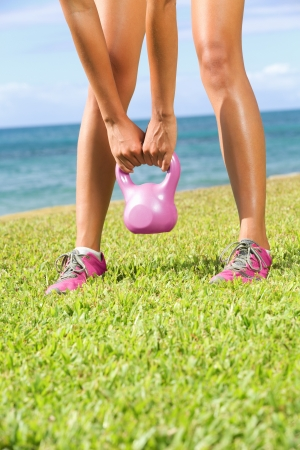 Kettlebell fitness training woman during crossfit exercise outside. photo