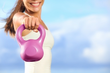 Kettlebells. Kettlebell training fitness woman - closeup of hand lifting kettlebell outside against blue sky with copy space. photo