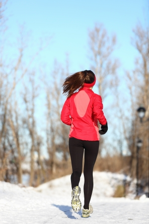 Winter running woman jogging in snow. Female runner in full body. Active lifestyle and wellness concept with young woman fitness model. photo