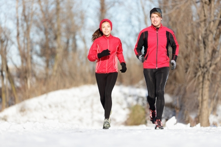 Sport couple running in winter. Runners jogging in snow in city park. Interracial young happy couple enjoying healthy lifestyle. Asian woman fitness model and caucasian man. photo