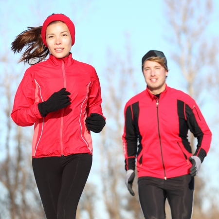 Healthy lifestyle winter running. Runner couple jogging in city park in warm winter sports clothing. Fit Asian woman fitness model and Caucasian man model. photo