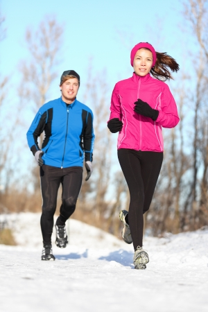 winter couple: Young couple running dressed warmly in fleeces and gloves jogging in sunshine across winter snow in the countryside