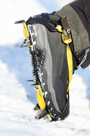 crampons: Crampons closeup. Crampon on winter boot for climbing, glacier walking or hiking and trekking on ice and hard snow. Stock Photo