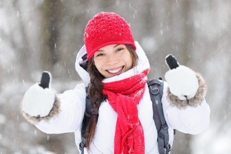 warmly: Happy young Asian woman with a beautiful vivacious smile dressed warmly in winter clothes standing outdoors in a snowstorm giving thumbs up gesture of approval