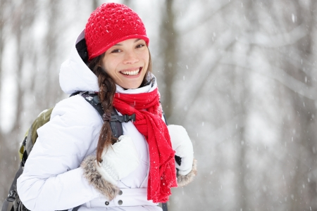 grinning: Woman winter hiking. Beautiful young Asian woman enjoying the falling snow dressed in a cheerful red winter scarf and cap and with a satchel on her back with copyspace.