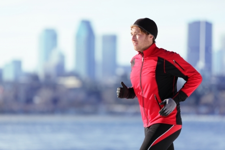 Athlete man running sport. Runner in winter jogging outdoors with city skyline in background. Male fitness model in Montreal, Canada. photo