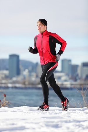 winter sports: Fitness running man. Male runner training and jogging outdoors in winter snow with cityscape skyline in background. Wellness workout and healthy lifestyle concept with Caucasian male fitness model in Montreal, Quebec, Canada. Stock Photo