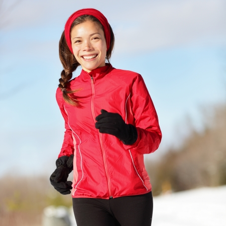 Fitness running woman. Closeup of female runner training and jogging outdoors in winter snow. Wellness workout and healthy lifestyle concept with mixed race Asian / Caucasian female fitness model. photo