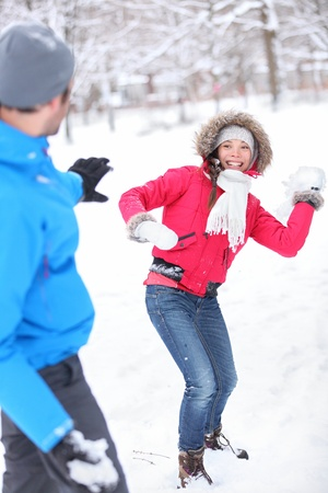 Young couple playing in the snow in snowball filght with a vivacious smiling Asian girl taking aim at her husband with a snowball photo