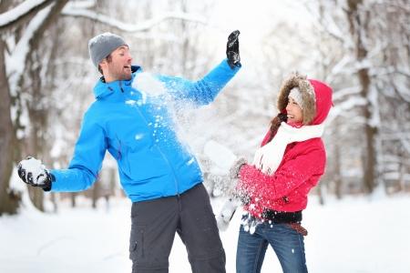 bolas de nieve: Despreocupado joven pareja feliz divirti�ndose juntos en nieve en invierno bosque lanzando bolas de nieve unos a otros durante un simulacro de lucha
