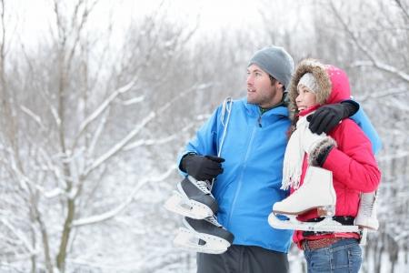 patinando: Joven pareja interracial en patines de hielo de invierno que llevan de pie juntos mirando hacia fuera sobre un paisaje de invierno cubierto de nieve con copyspace. Mujer asi�tica, hombre cauc�sico.