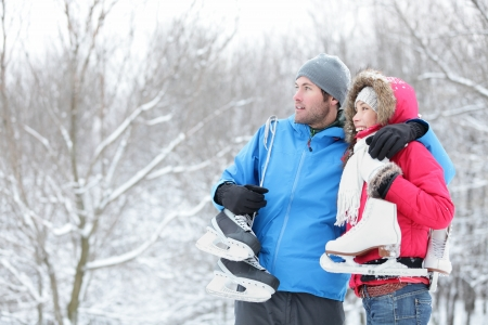 man looking out: Young interracial couple in winter carrying ice skates standing close together looking out over a snowy winter landscape with copyspace. Asian woman, Caucasian man.