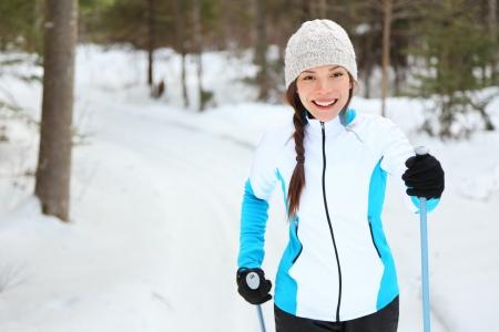 narciarz: Biegi narciarskie kobieta robi klasyczne narciarstwo biegowe w torach szlaku w pokryte śniegiem las w Quebec, Kanada Zdjęcie Seryjne