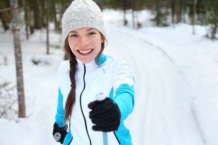 canada country: Cross-country skiing woman doing classic nordic cross country skiing in trail tracks in snow covered forest in Quebec, Canada