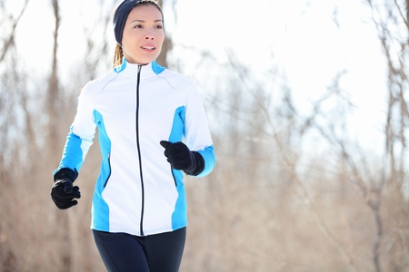 Running young Asian woman jogging in a winter fleece and gloves in open countryside with copyspace in a health and fitness concept photo
