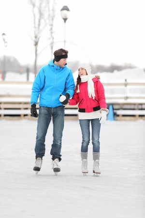 Young couple holding hands iceskating outdoors on a frozen lake or open-air rink against a snowy winter landscape photo