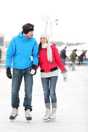 skaters: Romantic young couple in warm winter clothing holding hands and smiling at each other while ice skating.