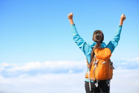 backpackers: Winner   Success concept  Hiker woman cheering elated and blissful with arms raised in the sky after hiking to mountain top summit above the clouds