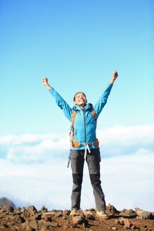 winning woman: Happy blissful hiker woman in winning   success concept  Hiker woman cheering joyful in bliss with arms raised in the sky after hiking to mountain top summit above the clouds  Asian female model