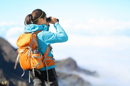 woman searching: Hiker looking in binoculars enjoying spectacular view on mountain top above the clouds