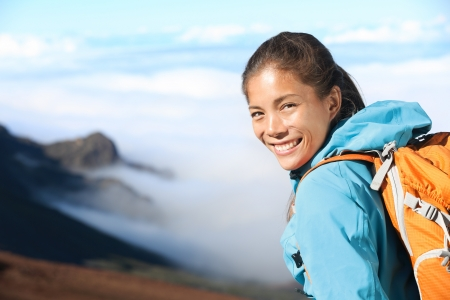 blissful: Hiker portrait of young woman hiking in high mountains  Beautiful blissful serene smiling happy mixed race Asian   Caucasian woman outdoors in big nature