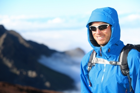 outdoorsman: Hiker man trekking portrait in high mountain  Hiking male in alpine clothing hard shell jacket above in mountain above the clouds  Portrait of young man outdoorsman
