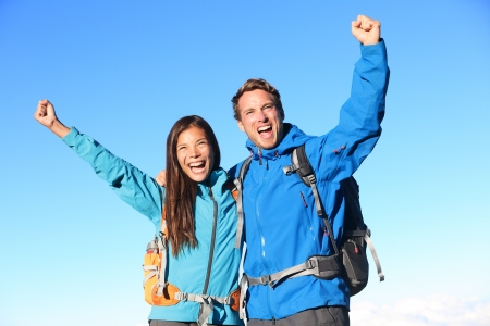 trekker: Happy hiking couple cheering in winning success concept  Young woman and man hiker holding around eachother elated and cheerful with arms raised in the sky  Asian girl and Caucasian male hikers