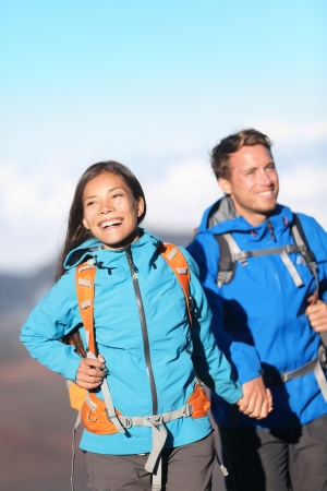 Happy interracial couple hiking holding hands on mountain hike  Sporty young couple walking outside high in mountains  Joyful cheerful Asian girl and Caucasian man hikers  photo