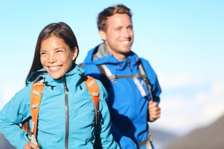 Hikers - hiking couple smiling happy walking cheerful in mountains with backpack  Asian woman hiker with Caucasian man hiker  photo