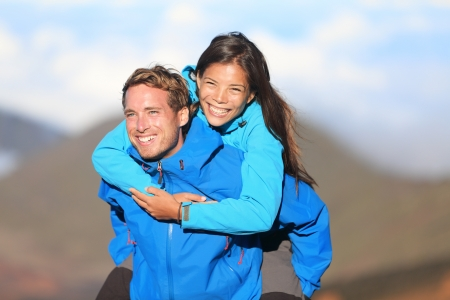 interracial relationships: Happy hiking couple piggyback having fun on hike  Fresh young blissful interracial couple  Asian woman hiker and Caucasian man hiker  Stock Photo