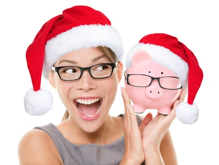 christmas savings: Christmas glasses eyewear sale concept  Woman wearing eye glasses and santa hat is holding piggy bank with glasses  Excited multiracial young woman isolated on white background