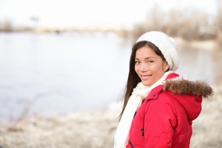 Winter woman portrait outside  Mixed-race girl smiling happy in cold winter landscape wearing warm winter clothing smiling happy looking at camera  Asian Chinese and Caucasian ethnicity  From Quebec, Canada  photo