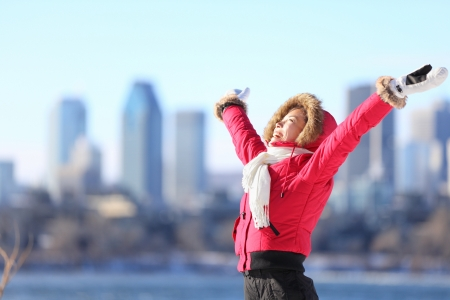 arms raised: City winter woman happy standing excited and elated with arms raised in joy  Beautiful young woman and Montreal City skyline, Quebec, Canada  Stock Photo