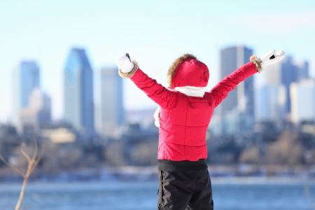 Happy winter woman in city excited and cheering with arms raised in happiness  Beautiful young woman and Montreal City skyline, Quebec, Canada