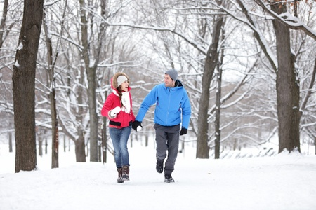 Couple walking and running in winter forest happy and joyful holding hands on romantic date in winter snow forest landscape  Cheerful interracial young couple, Asian woman, Caucasian man  photo