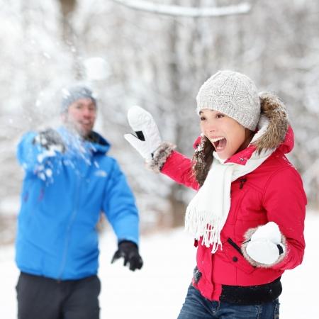 palle di neve: Divertimento invernale - coppia in battaglia a palle di neve divertirsi insieme nel paesaggio forestale neve Felice giovane coppia interrazziale che giocano insieme nella neve