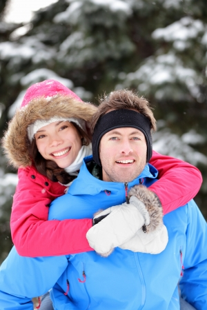 Happy young couple in winter having fun embracing having fun together in winter snow forest  Young interracial couple, Asian woman, Caucasian man  Stock Photo - 15720976