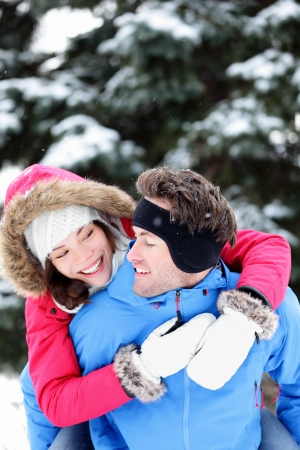 couple winter: Happy winter couple having fun doing piggyback in snow winter landscape outside in forest  Beautiful young interracial couple piggybacking