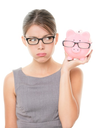 Upset woman wearing glasses holding piggy bank   photo