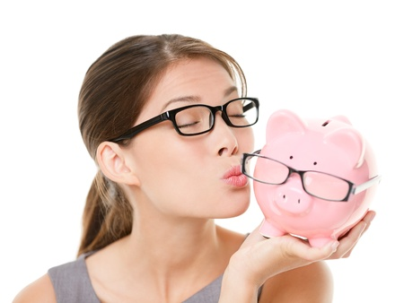 funny glasses: Glasses sale concept  Happy woman kissing piggy bank wearing eyewear glasses