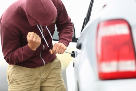 stealing: View down the side of a car to a man in a hooded top breaking into a car with a screwdriver in order to steal it Stock Photo