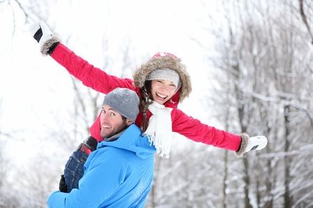 Winter fun couple playful together during winter holidays vacation outside in snow forest photo