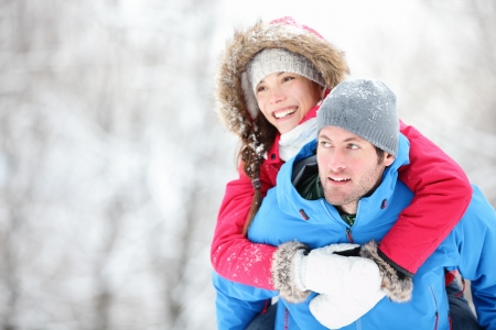 Man giving woman piggyback ride on winter vacation in snowy forest   Stock fotó