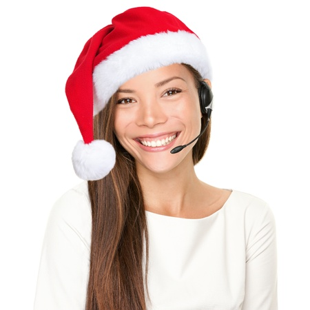 virtual assistant: Christmas headset woman from telemarketing call center wearing red santa hat talking smiling isolated on white background