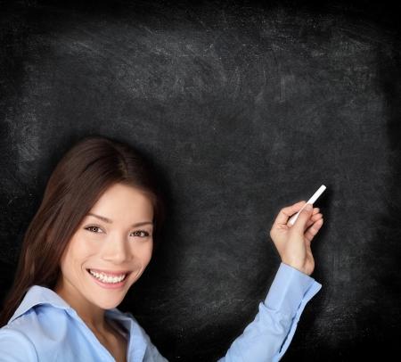 maestra ense�ando: Profesor de ense�anza o escritura joven estudiante en la pizarra pizarra con tiza un espacio de la copia para su texto Foto de archivo