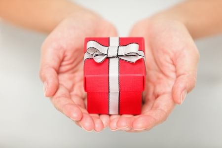 winning proposal: Gift. Woman holding showing gift or christmas gift in her hands. Female hands giving red present. Stock Photo