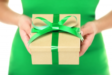 package: Gift  present. Woman hands showing and giving gifts. Closeup of present made of recycled carton and green ribbon on white background.
