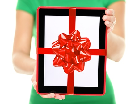 Closeup of woman showing and giving digital tablet computer as present or christmas gift photo